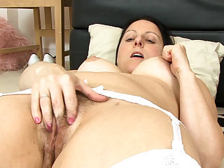 Dark-haired milf Amber Lustfull is sucking her nipples and fingering sweet hairy pussy